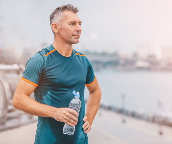 man in exercise clothes holding water